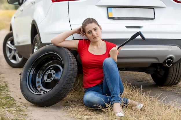 Mulher jovem sentada no chão em um carro quebrado e olhando para a chave de roda