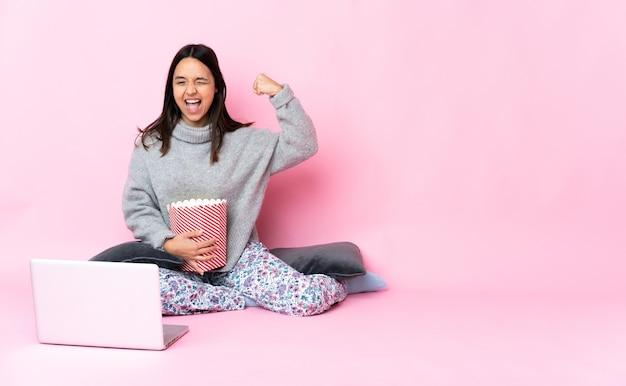 Mulher jovem sentada no chão exibindo um filme em um laptop