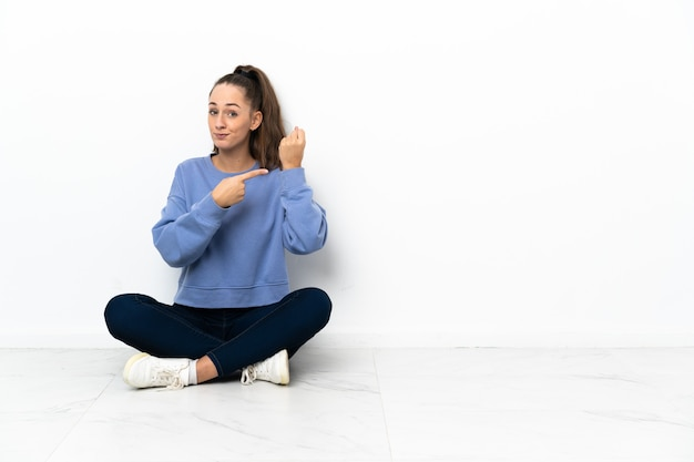Mulher jovem sentada no chão fazendo o gesto de se atrasar