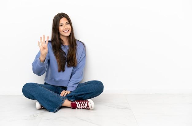 Mulher jovem sentada no chão feliz contando quatro com os dedos