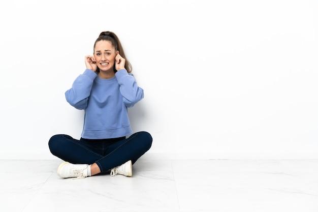 Mulher jovem sentada no chão frustrada e cobrindo as orelhas