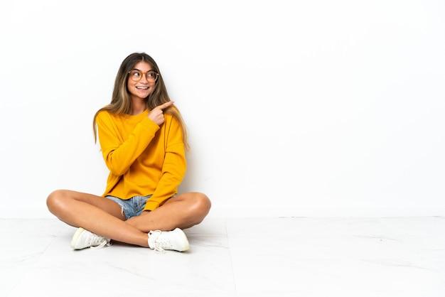 Mulher jovem sentada no chão isolada no fundo branco apontando para o lado para apresentar um produto