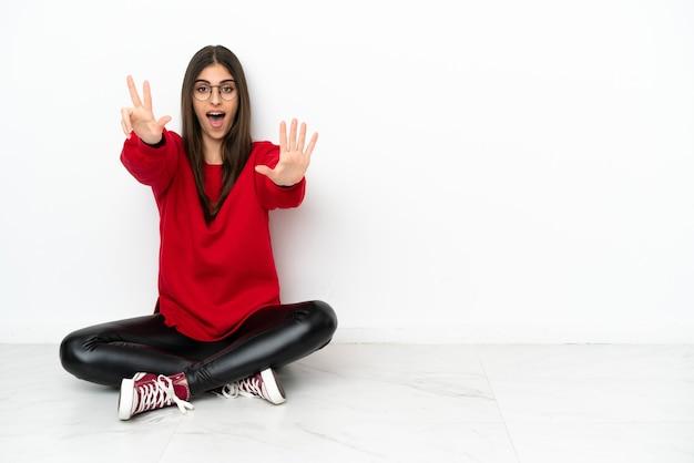 Mulher jovem sentada no chão, isolada no fundo branco, contando oito com os dedos
