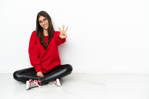 Mulher jovem sentada no chão, isolada no fundo branco, feliz e contando três com os dedos