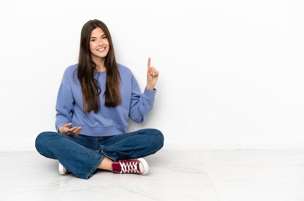 Mulher jovem sentada no chão mostrando e levantando um dedo em sinal dos melhores