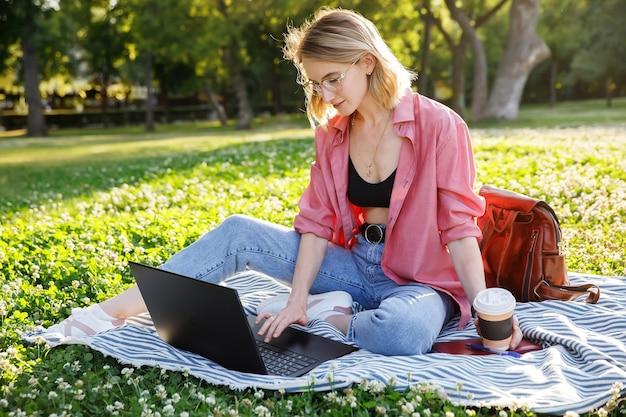 Mulher jovem sentada no gramado do parque usa laptop