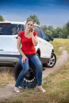 Mulher jovem sentada no pneu sobressalente na beira da estrada e pedindo ajuda