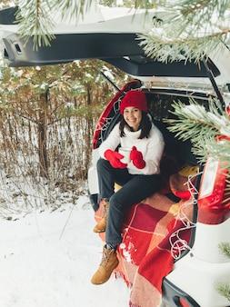 Mulher jovem sentada no porta-malas do carro bebendo chá quente em um dia de neve de inverno