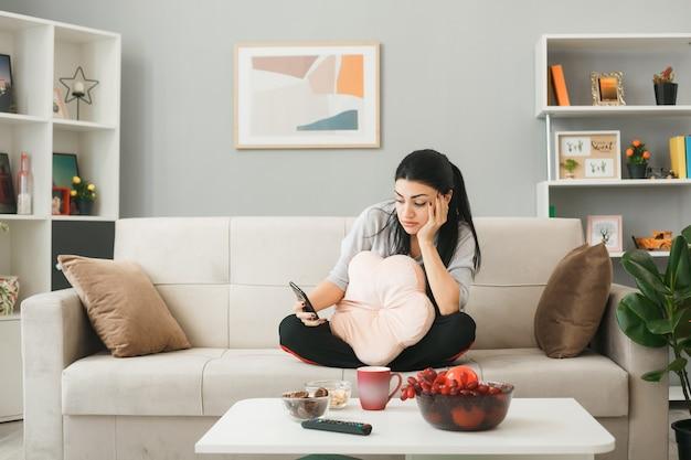 Mulher jovem sentada no sofá atrás da mesa de centro com uma almofada, segurando e olhando para o telefone na sala de estar