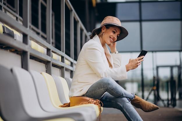 Mulher jovem sentada nos assentos da arena e falando ao telefone