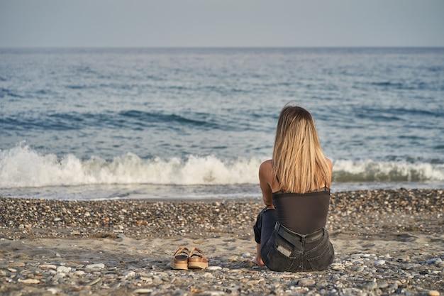 Mulher jovem sentada olhando para o horizonte com chinelos na areia da praia