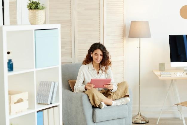 Mulher jovem sentada relaxada na poltrona e fazendo seu trabalho usando um computador tablet moderno e a internet