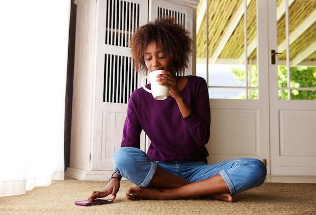 Mulher jovem, sentando, casa, com, café, e, telefone móvel