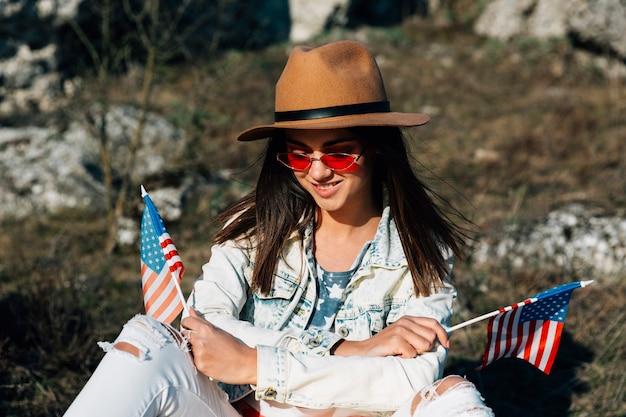 Mulher jovem, sentando, com, bandeiras, de, estados unidos, ligado, natureza