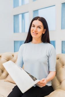 Mulher jovem, sentando, com, jornal, ligado, sofá