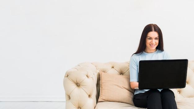 Mulher jovem, sentando, com, laptop, ligado, sofá