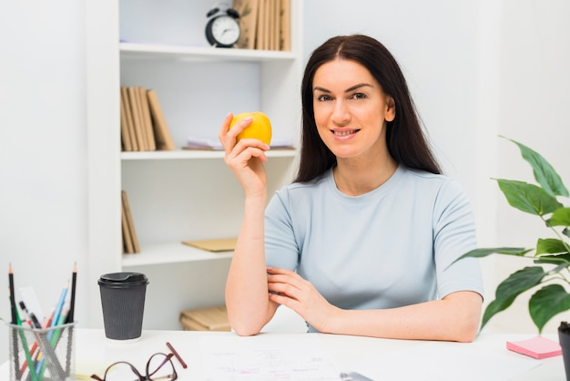 Mulher jovem, sentando, com, maçã, em, escritório