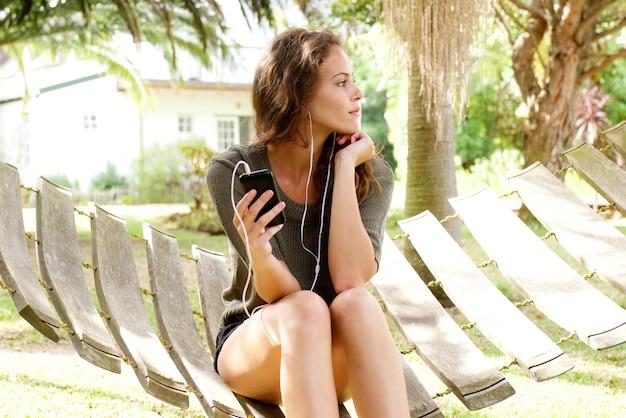 Mulher jovem, sentando, em, quintal, escutar música