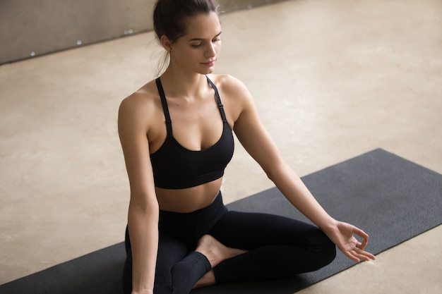 Mulher jovem, sentando, em, sukhasana, pose, com, mudra, cinzento, estúdio