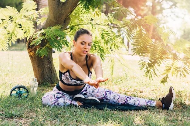 Mulher jovem, sentando, frente, árvore, fazendo, esticando exercício