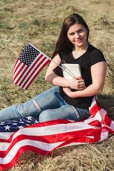 Mulher jovem, sentando, ligado, listra, bandeira, e, bandeira americana segurando