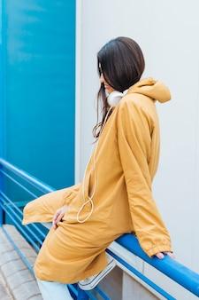 Mulher jovem, sentando, ligado, metálico, azul, trilhos, desgastar, headphone, ligado, dela, pescoço