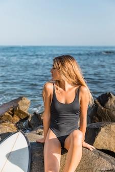 Mulher jovem, sentando, ligado, rocha, com, surfboard