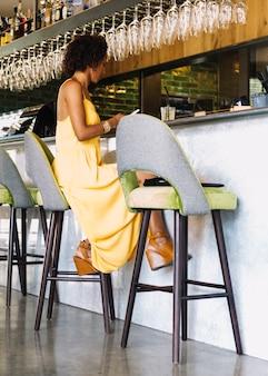 Mulher jovem, sentando, ligado, tamborete barra, usando, smartphone, em, a, restaurante