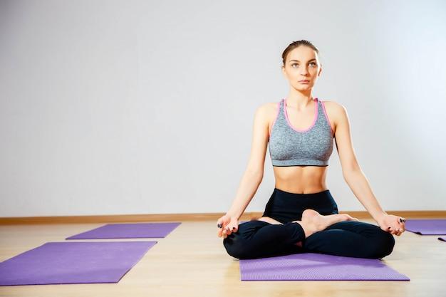 Mulher jovem, sentar chão, em, posição lotus, enquanto, meditar