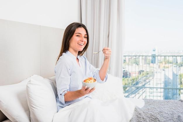 Mulher jovem, sentar-se cama, desfrutando, a, salada fruta