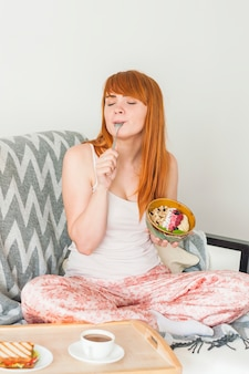 Mulher jovem, sentar sofá, comer, aveia, granola, café manhã