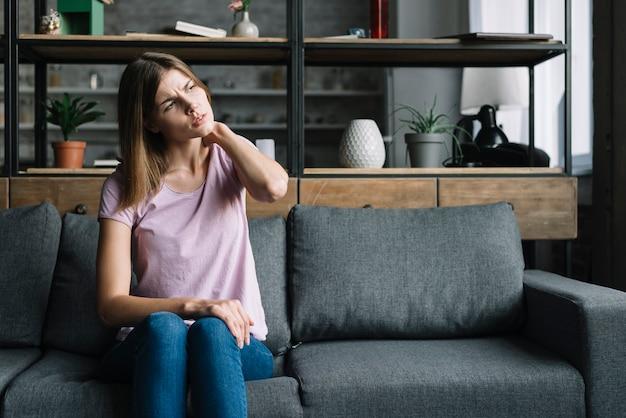 Mulher jovem, sentar sofá, tendo, pescoço, dor