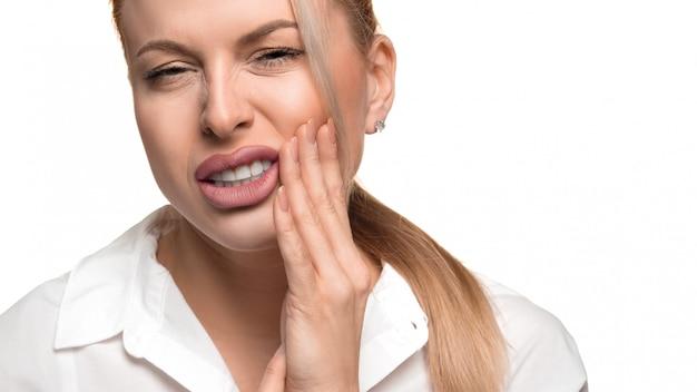 Mulher jovem sente forte dor de dente. conceito de saúde bucal.