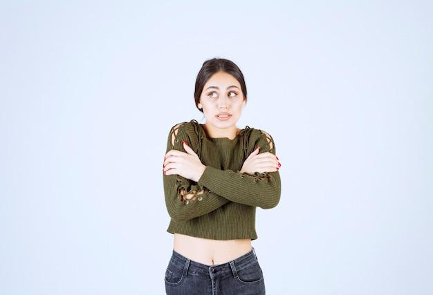 Mulher jovem, sentindo-se extremamente fria em fundo branco.