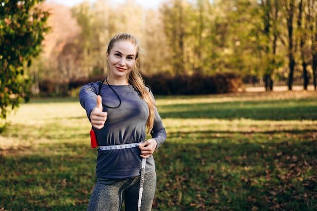Mulher jovem, sentindo-se feliz, medindo a cintura após treino