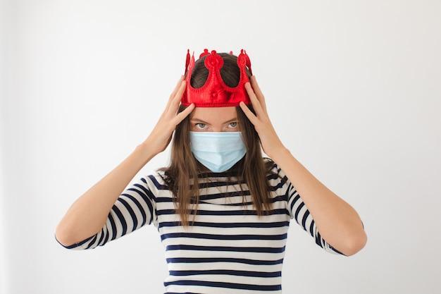 Mulher jovem séria com roupas casuais e máscara protetora com coroa vermelha na cabeça, representando o conceito de pandemia de coronavírus