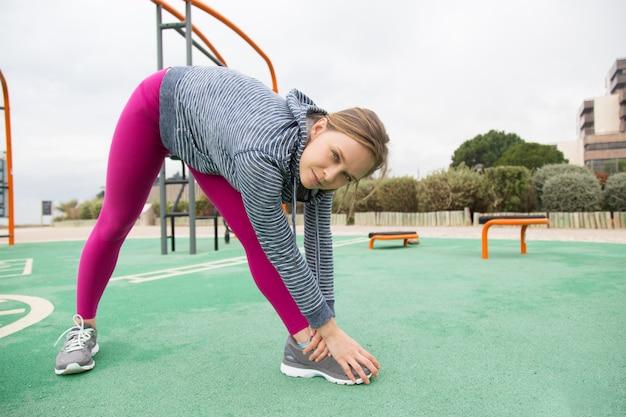 Mulher jovem séria, dobrando-se e esticando as pernas no chão de esportes