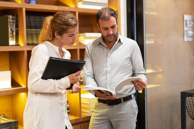 Mulher jovem séria e homem adulto médio assistindo a revista