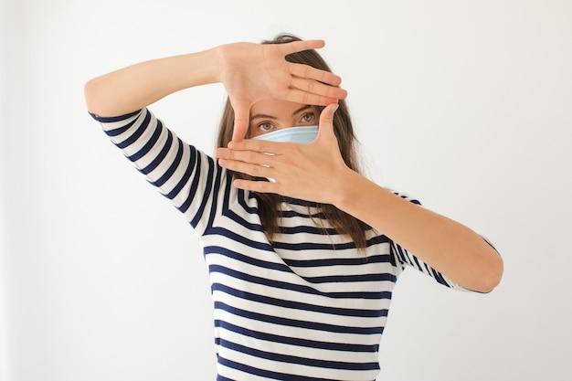 Mulher jovem séria em camisa casual listrada e máscara protetora para prevenção de coronavírus olhando para a câmera com as mãos