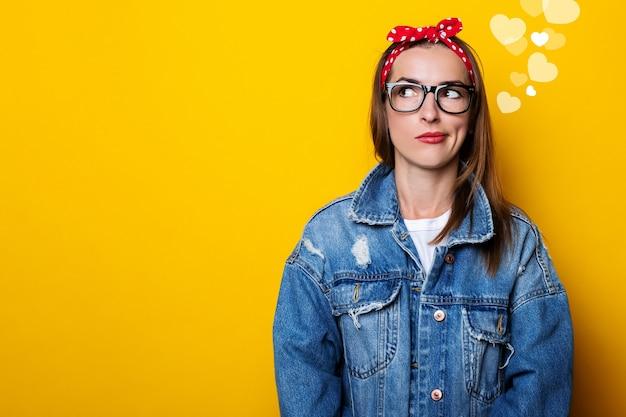 Mulher jovem séria em uma faixa de cabelo, em uma jaqueta jeans e óculos parece para o lado em uma parede amarela.