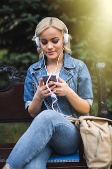 Mulher jovem séria feliz ouvindo música em fones de ouvido e usando o smartphone enquanto está sentado no banco da cidade