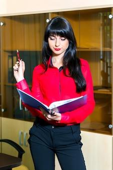 Mulher jovem séria na blusa vermelha com uma pasta de documentos no escritório