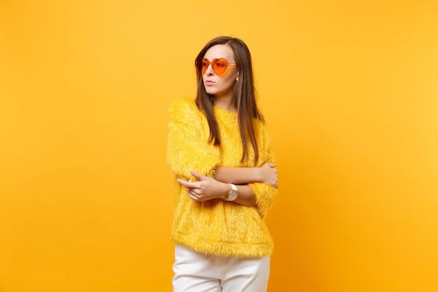Mulher jovem séria no suéter de pele e óculos coração laranja olhando de lado, de mãos postas isoladas no fundo amarelo brilhante. emoções sinceras de pessoas, conceito de estilo de vida. área de publicidade.