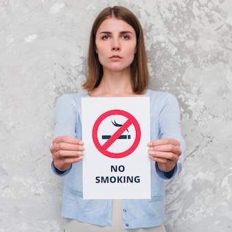 Mulher jovem séria segurando papel de mensagem social de não fumar