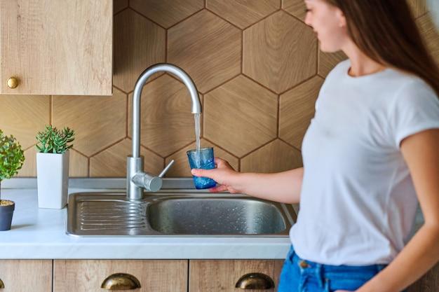 Mulher jovem servindo água corrente da torneira filtrada e purificada em vidro na cozinha para uma bebida saudável