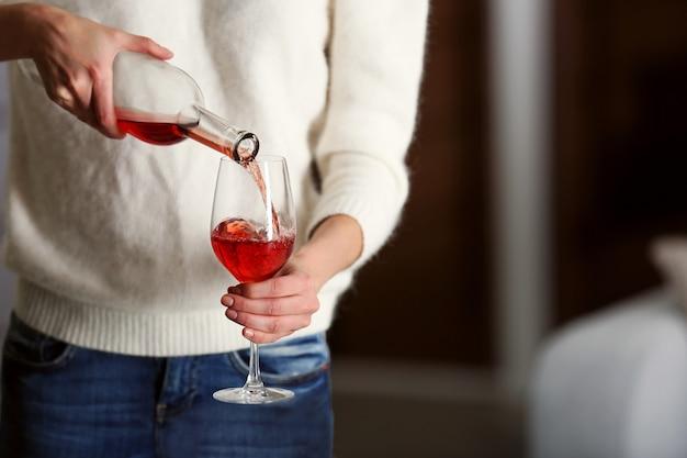 Mulher jovem servindo vinho rosa no copo