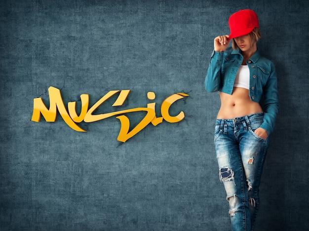 Mulher jovem sexy com roupas da moda em uma parede de grunge. parede musical