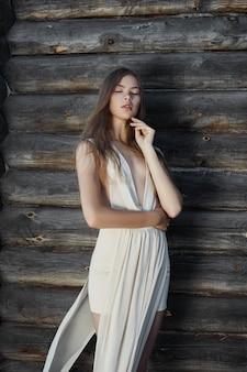 Mulher jovem sexy com um vestido branco claro, posando na aldeia perto da velha casa. menina com uma figura perfeita no fundo de uma casa de campo de toras