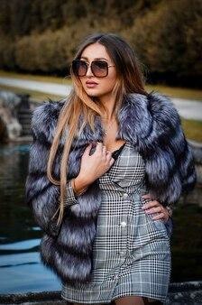Mulher jovem sexy elegante em óculos de sol, casaco de pele e vestido curto posando ao ar livre.