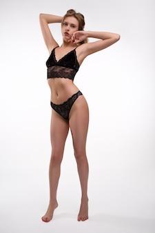 Mulher jovem sexy em lingerie de renda preta em pé com as mãos levantadas